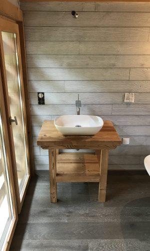 Pose d'un lavabo vasque sur un plan de travail en bois dans une suite parentale